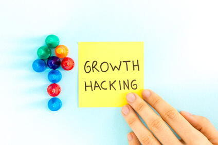 """Growth hacking"" note with arrow pointing up, on blue background."